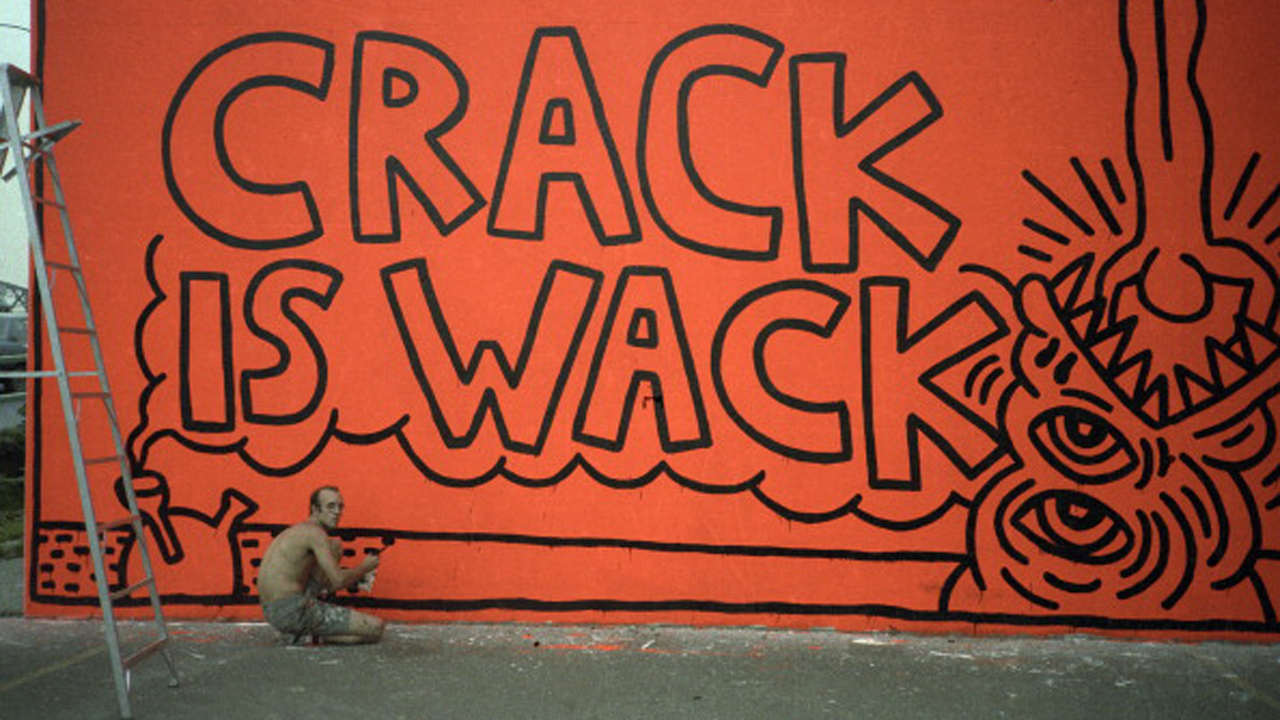 American pop artist and activist Keith Haring (1958 - 1990) paints the original version of his 'Crack is Wack' mural on the wall of a hand ball court in a public park (at East 128th Street and 2nd Avenue, alongside Harlem River Drive), New York, New York , summer 1986. This first version of the mural, painted in response to the then-ongoing epidemic of crack cocaine usage in New York, was executed illegally and was subsequently completely repainted with different imagery (and legally, with the blessing of the city's government who renamed the park the 'Crack is Wack Playground') at least once by Haring in the following months. (Photo by Juan Rivera/Roulette Fine Art/Getty Images)